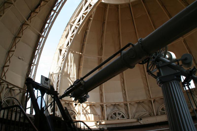 Lunette astronomique de l'Observatoire de Strasbourg sous sa coupole. L'intérieur de la coupole est beige, elle est entre-ouverte et la lunette de couleur gris métallique et dans l'axe de l'ouverture.
