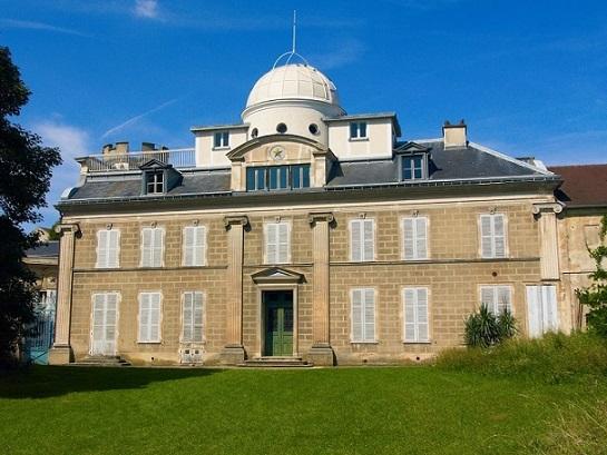 Vue depuis le parc (sol avec de l'herbe verte) de l'Observatoire Camille Flammarion. On voit le bâtiment sur deux étages, grande demeure avec en haut sur le toit une coupole blanche de 5mètres.