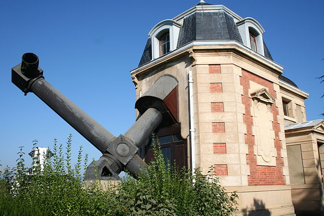 Bâtiment historique de l'Observatoire de Lyon, en briques rose clair et blanches, toit noir, d'où dépasse la lunette coudée de couleur gris anthracite. En fond le ciel est bleu.