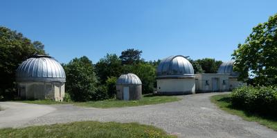 Sous un ciel bleu, trois coupoles de l'Observatoire de Lyon ensoleillées (toits bleu clair et murs blancs), séparées par un chemin goudronné et des surfaces d'herbe verte.