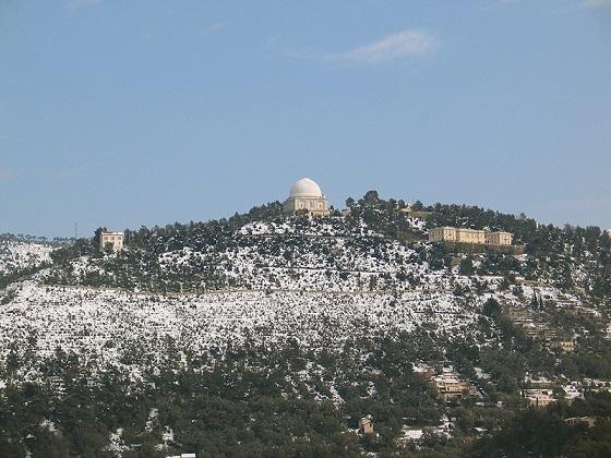 Vue du Mont Gros sur les hauteurs de Nice. De loin, on voit de la végétation provençale et de la pierre blanche, au centre au sommet de la colline une coupole au toit blanc et sur la droite et la gauche un peu en contre-bas des bâtiments en pierres jaunes.