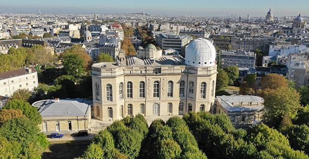 Vue en survol du bâtiment de l'Observatoire de Paris, en pierres blanches avec de grandes fenêtres. Il est entouré de verdure, et en fond on voit les toits de Paris.