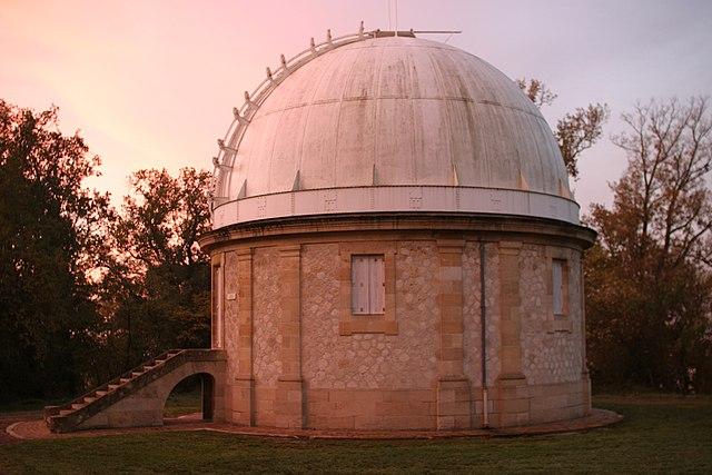 Coupole de l'Observatoire de Bordeaux, toit blanc et murs en pierres claires, en fin de journée donc avec une lumière dans les tons rose et violet.