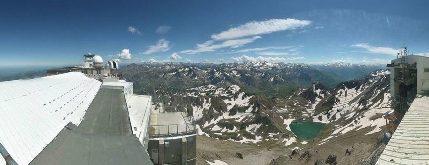 Vue panoramique depuis le Pic du Midi. De gauche à droite on voit le toit d'un des bâtiments, les coupoles blanches, au centre les montagnes avec un peu de neige et un lac bleu vert en contre-bas, le ciel est bleu, et à droite de l'image une autre partie des bâtiments.