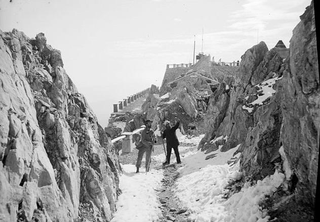 Photo en noir et blanc qui montre le site du Pic du Midi au début du XXe siècle. On voit à droite et à gauche une paroi rocheuse, au centre un chemin enneigé avec deux hommes debout regardant la roche, et derrière les premiers bâtiments de l'Observatoire.