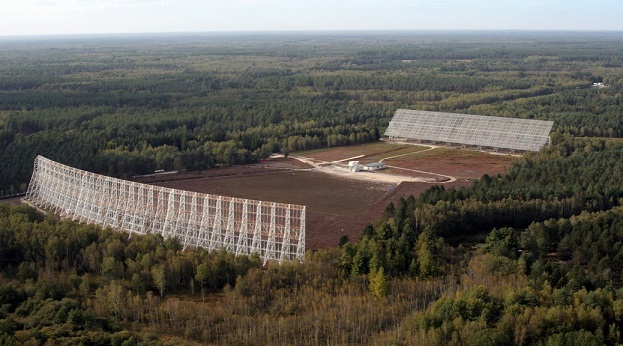 """Photo des deux grands miroirs du grand radiotélescope de Nançay face à face. Au milieu de la forêt, dans un champ, deux grands """"murs"""" blancs de 35 et 40 mètres de haut se font face."""