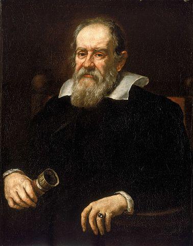 Tableau où l'on voit Galilée assis dans un fauteuil, la barbe grise, un vêtement noir avec col blanc, une bague à l'annulaire gauche et ce qui semble être une longue-vue dans la main droite.