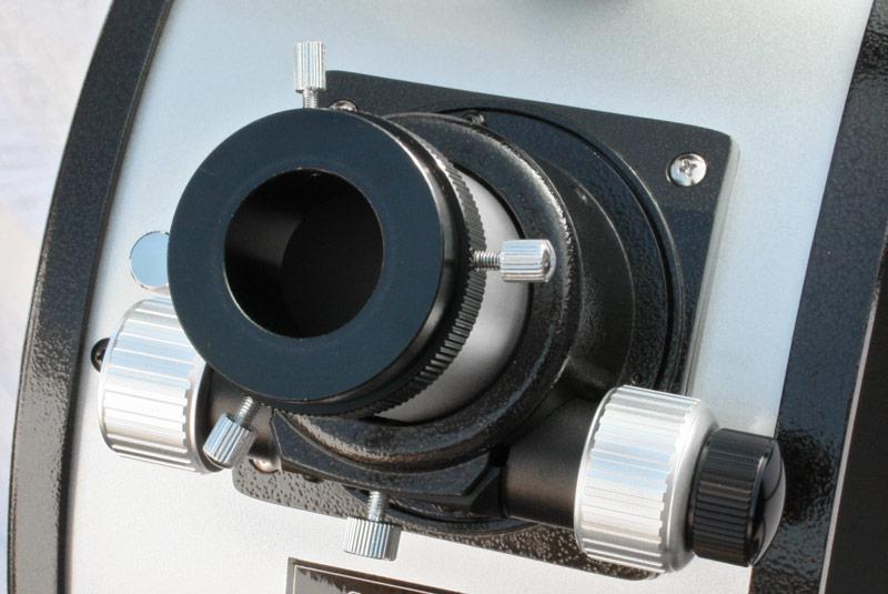 Photo d'un porte-oculaire de télescope où on voit les trois molettes de réglage de la mise au point. Les molettes grises ont un effet classique alors que la molette noire à droite permet un réglage plus fin.