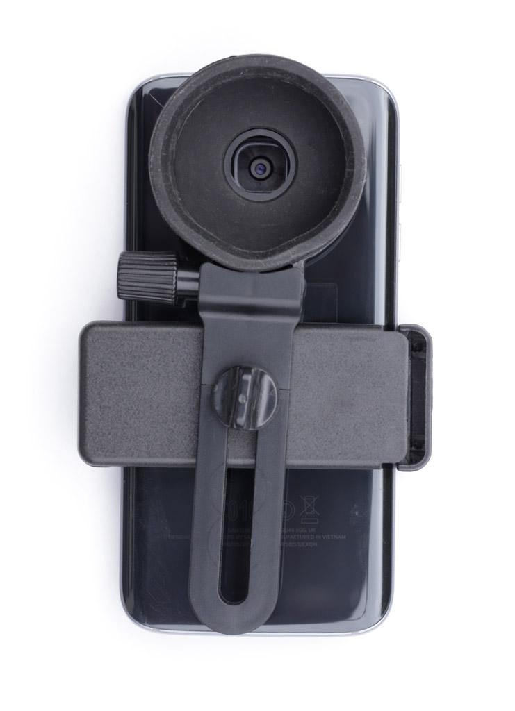 Photo d'un smartphone fixé sur son adaptateur, avec son objectif centré dans la fenêtre de visée.