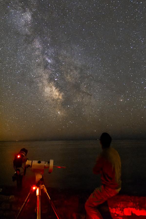 Photo représentant la voie lactée jusqu'à l'horizon, avec un observateur et son télescope, auteur Xavastro