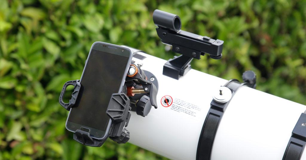 Photo montrant un smartphone fixé sur un télescope à l'aide d'un adaptateur spécifique.